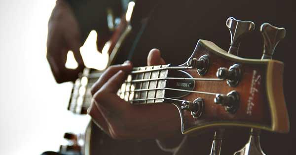 A bassist strumming a bass guitar.