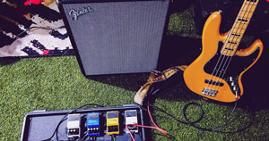 Guitar pedals, a guitar amp, and an electric guitar.