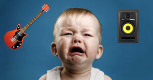 A crying baby surrounded by an electric guitar and studio monitor.
