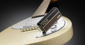 A portable amp plugged into the output jack of an electric guitar.
