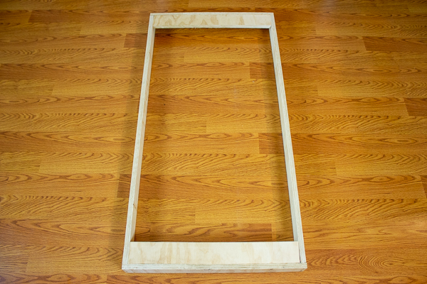 A rear view of two support strips added to an acoustic panel frame.