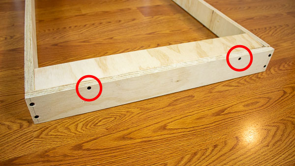 An image of a support strip held in place using wood glue and two wood screws (red).