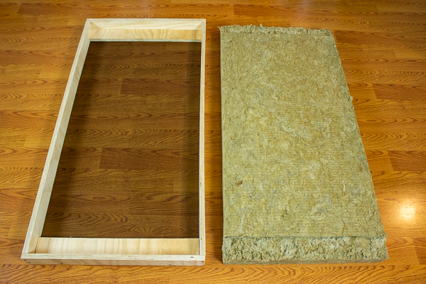 An image of insulation cut to fit inside an acoustic panel frame containing two support strips.