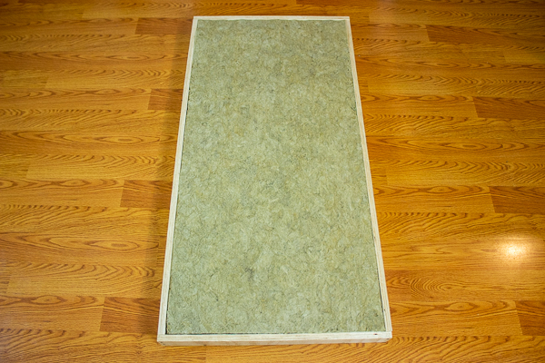 An image of insulation placed into the cavity of an acoustic panel's frame.