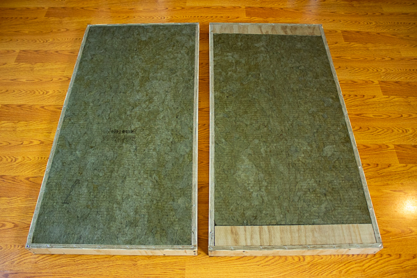 An image of fiberglass screen stapled to the front and back of two acoustic panel frames containing insulation.