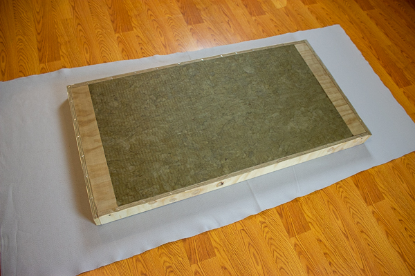 An image of an acoustic panel laying face down on a piece of felt.