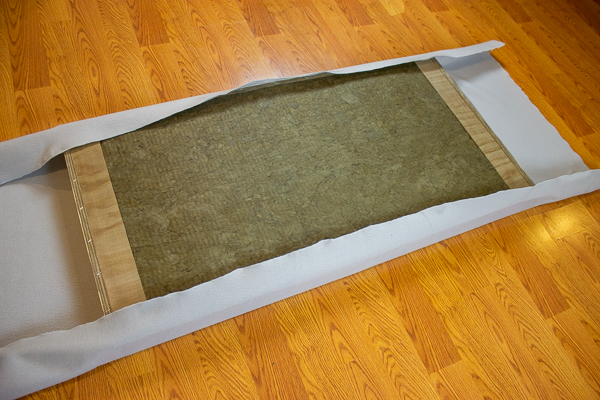 An image of an acoustic panel partially wrapped in felt using an adhesive spray.