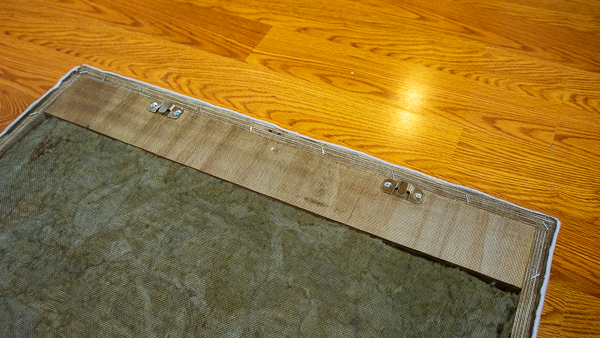 An image of flush mount brackets screwed into the back of an acoustic panel.