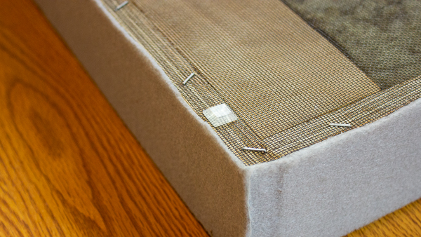 A close up view of a furniture bumper stuck onto the back of an acoustic panel.