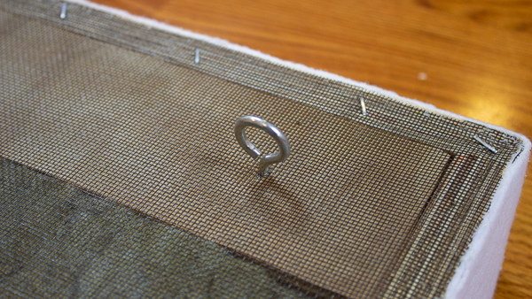 A close up view of a screw eye hook installed into the back of an acoustic panel.