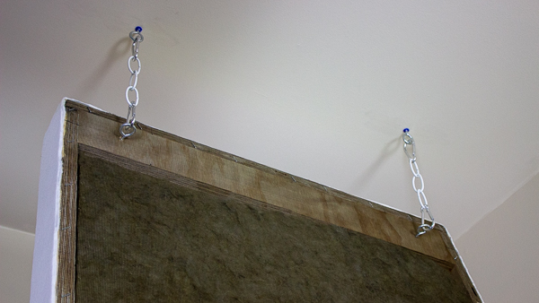 An image of an acoustic panel hanging from two suspension assemblies.