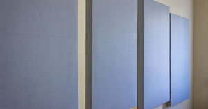 Homemade acoustic panels hanging on a wall.