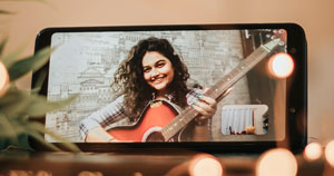 A guitarist appearing within the viewfinder of a mobile phone.