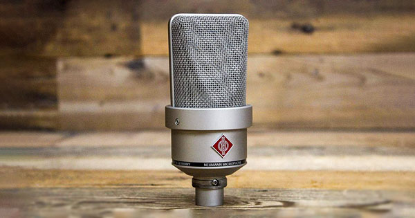 A TLM 103 microphone with a wooden background.