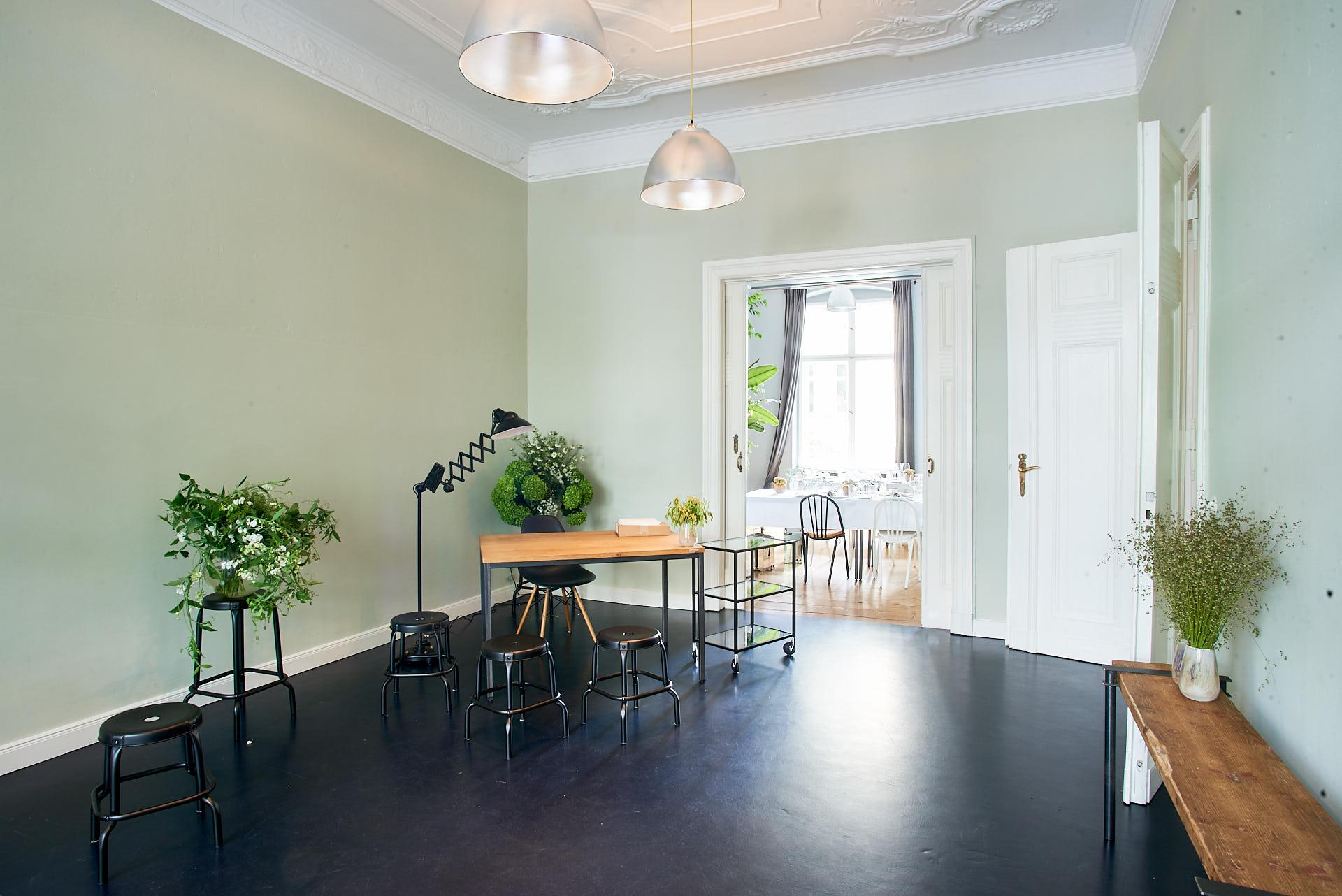 Foto eines Zimmers mit Artischocken-Motiv auf dem Boden, Schreibtisch und Stuhl