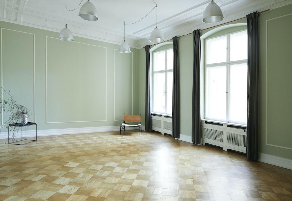 Foto mit Blick durch eine Tür in einen grünen Raum mit Stühlen