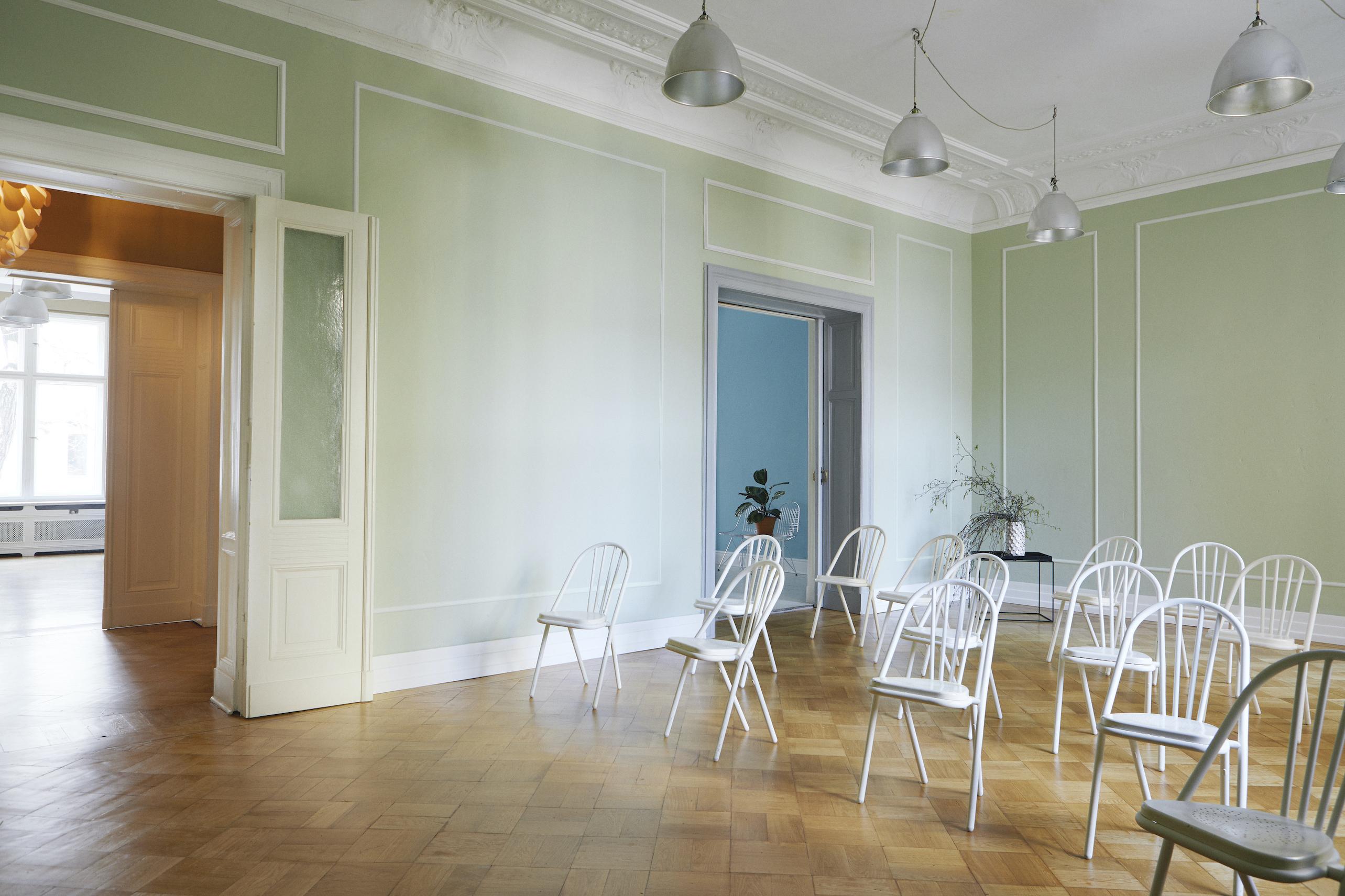 Foto eines grünes Altbauzimmer mit Tisch auf dem Pflanzen stehen