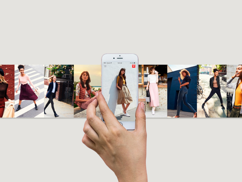 A hand holds an iPhone with a single frame of an image gallery of Uniqlo models. The image gallery extends beyond the frame of the iPhone on both sides.