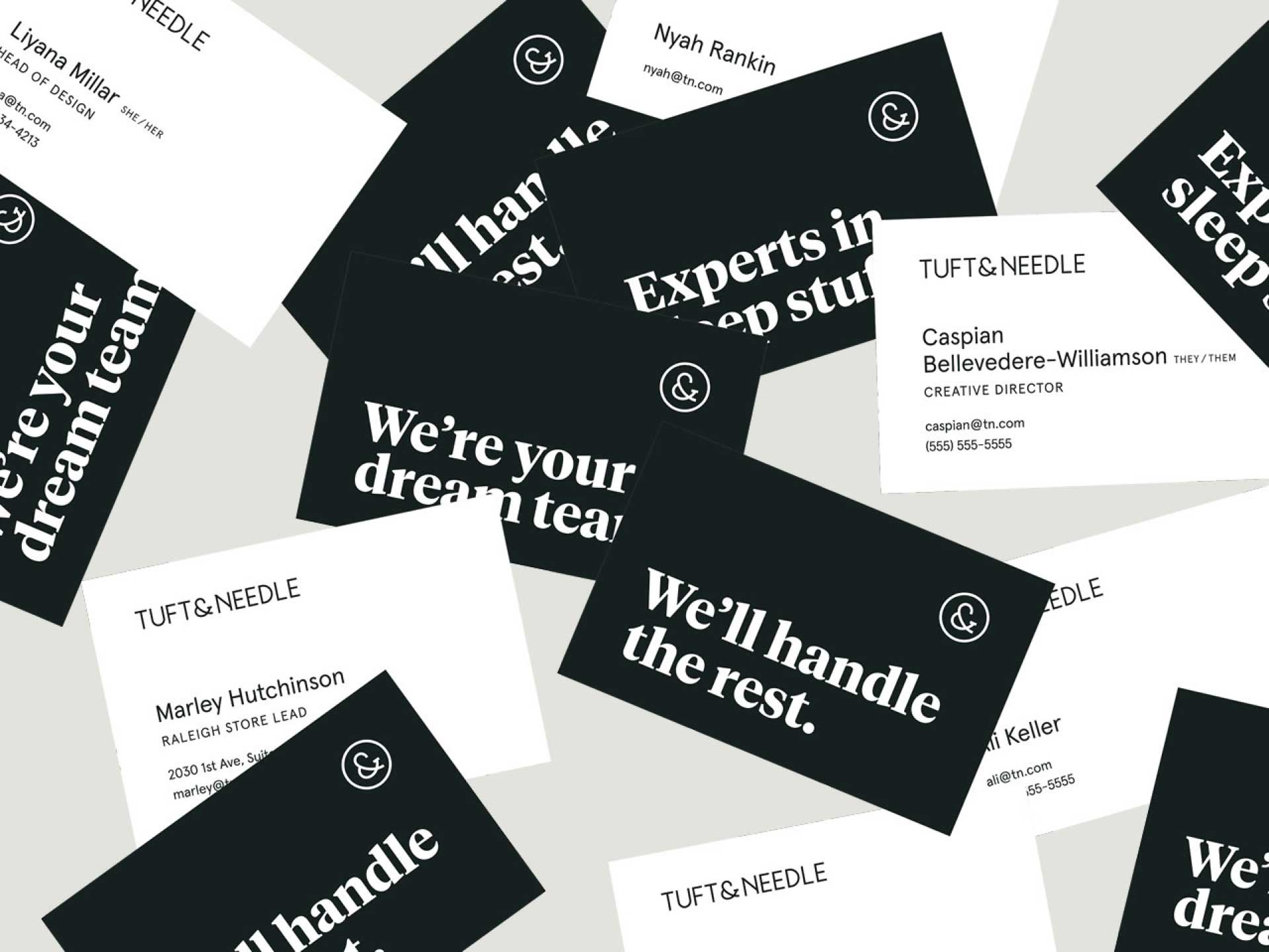 "Scattered business cards. Some of the cards show a dark gray side with one of three types of greetings that read ""We're your dream team,"" ""We'll handle the rest,"" and ""Experts in sleep stuff."" The others show a side that is white and has a simple typographic layout with the Tuft & Needle logo and different amounts of information on each card."