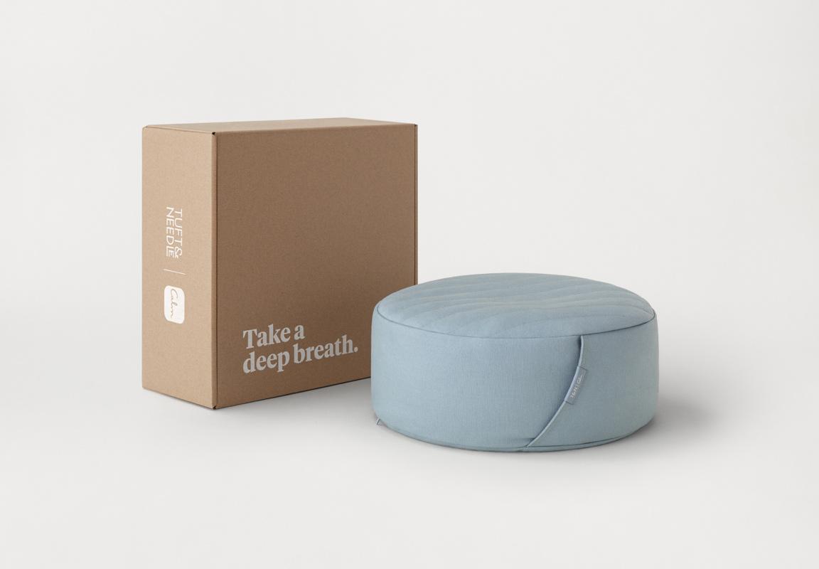 "A kraft box sits next to a light blue meditation cushion. A white headline on the box reads ""Take a deep breath."""