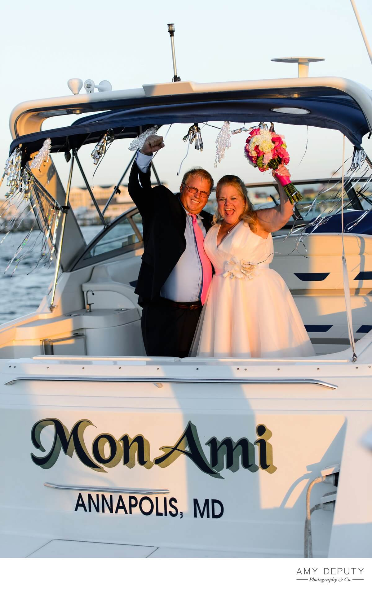 a bride and groom wave from a boat called mon ami from annapolis mar