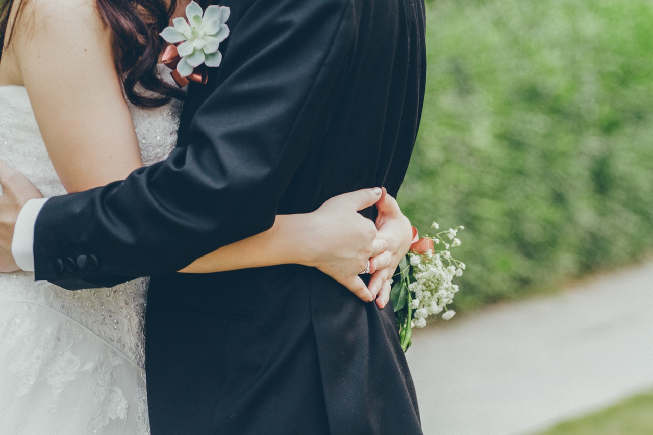 a bride and groom with their arms wrapped around one another