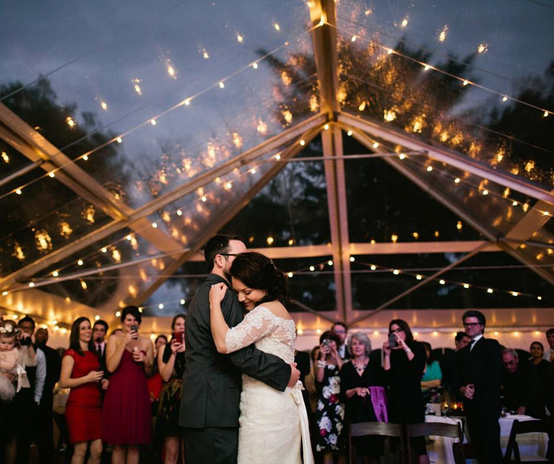 a bride and groom dance together surrounded by friends and family under twinkling lights