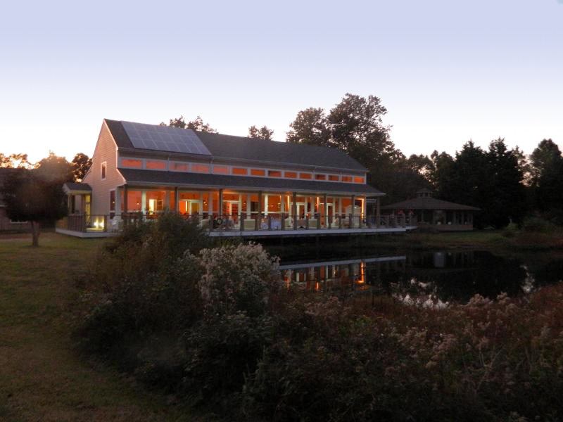 a building on a small pond is aglow in the fading light