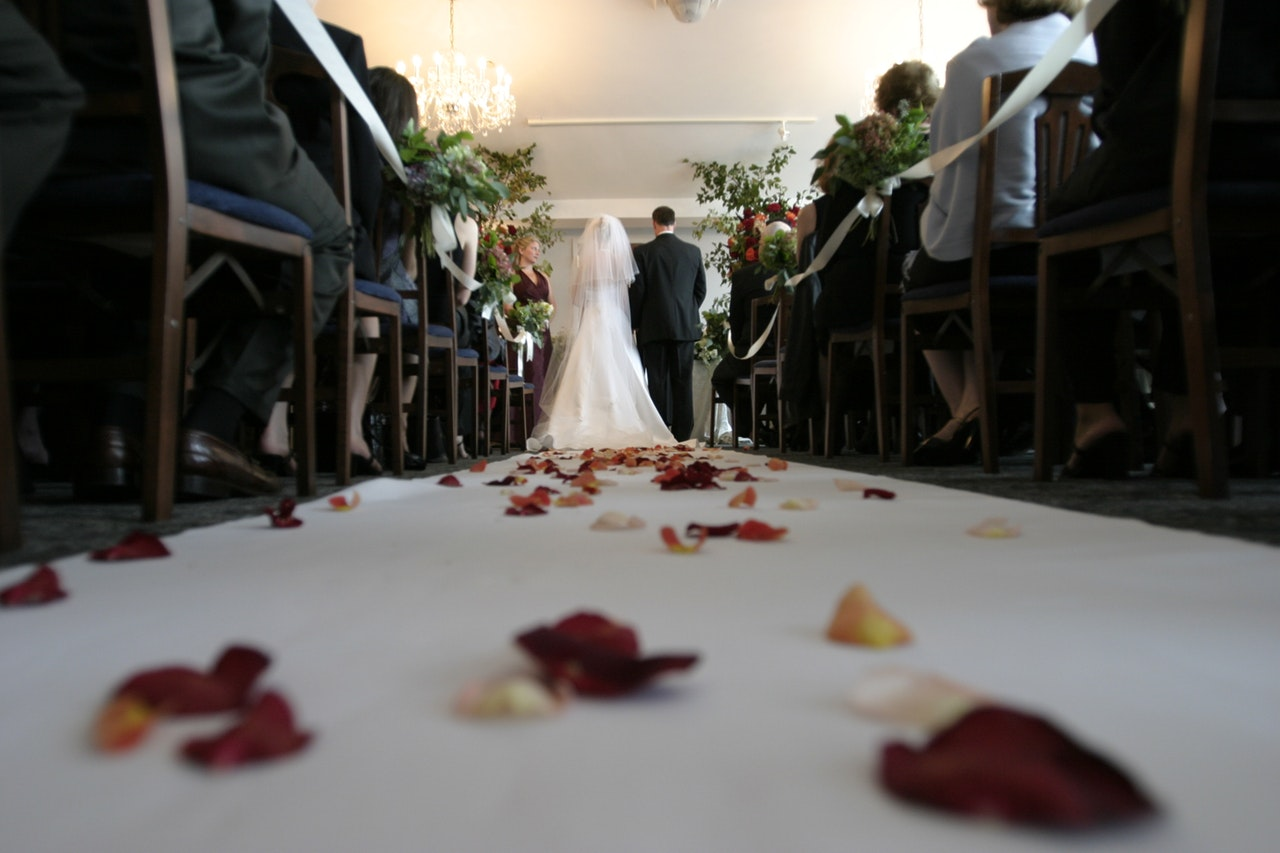 petals along the aisle of a church as a bride and groom stand at the altar