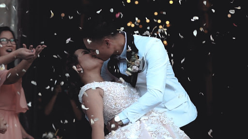 wedding couple kissing in front of confetti