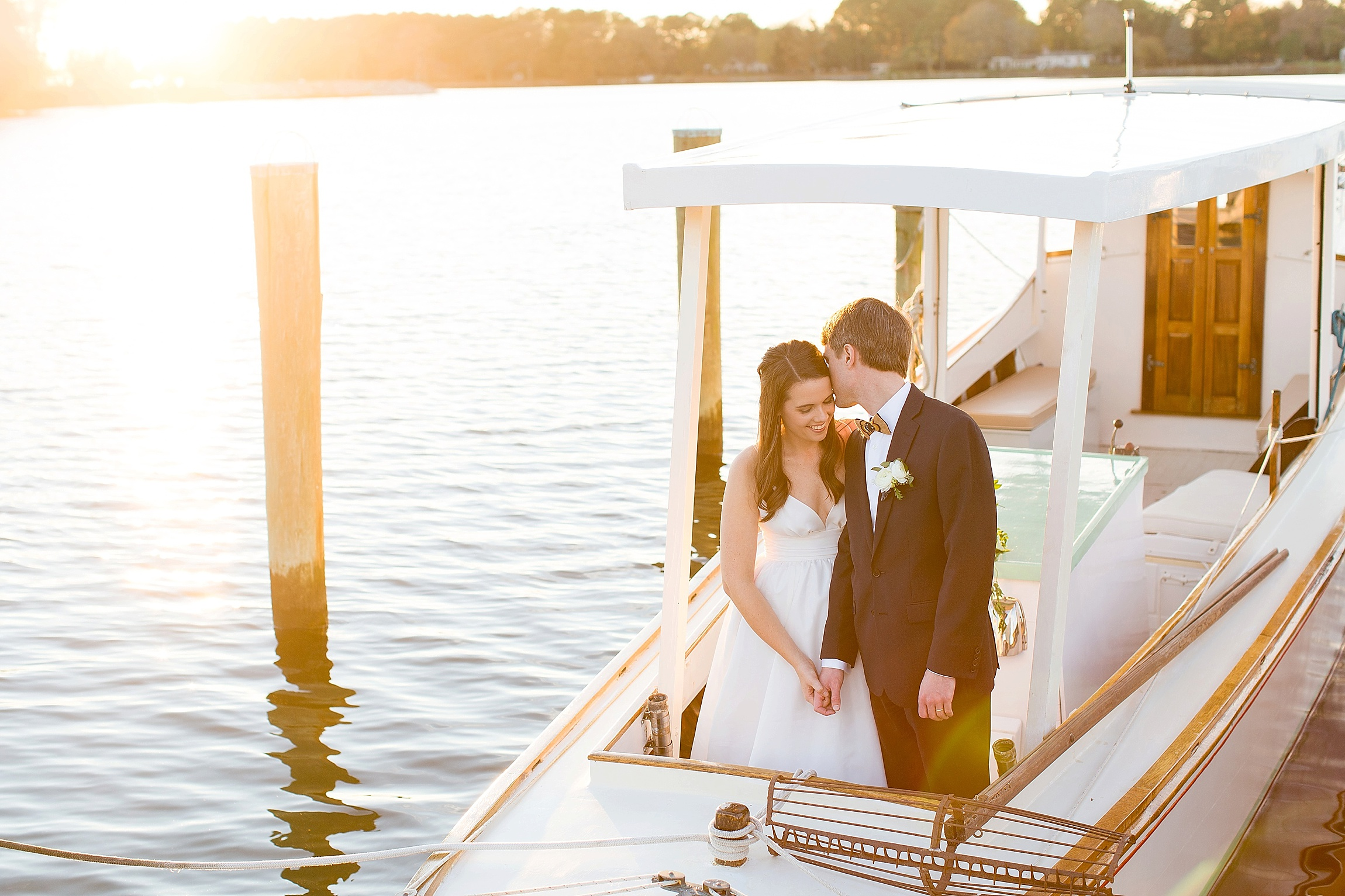 a bride and a groom kiss on a small boat at sunset
