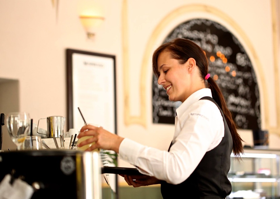 waitress carrying glass in restaurant