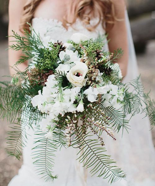 A rustic wedding bouquet with ferns, pieris, pinecones, and evergreens | Brides.com