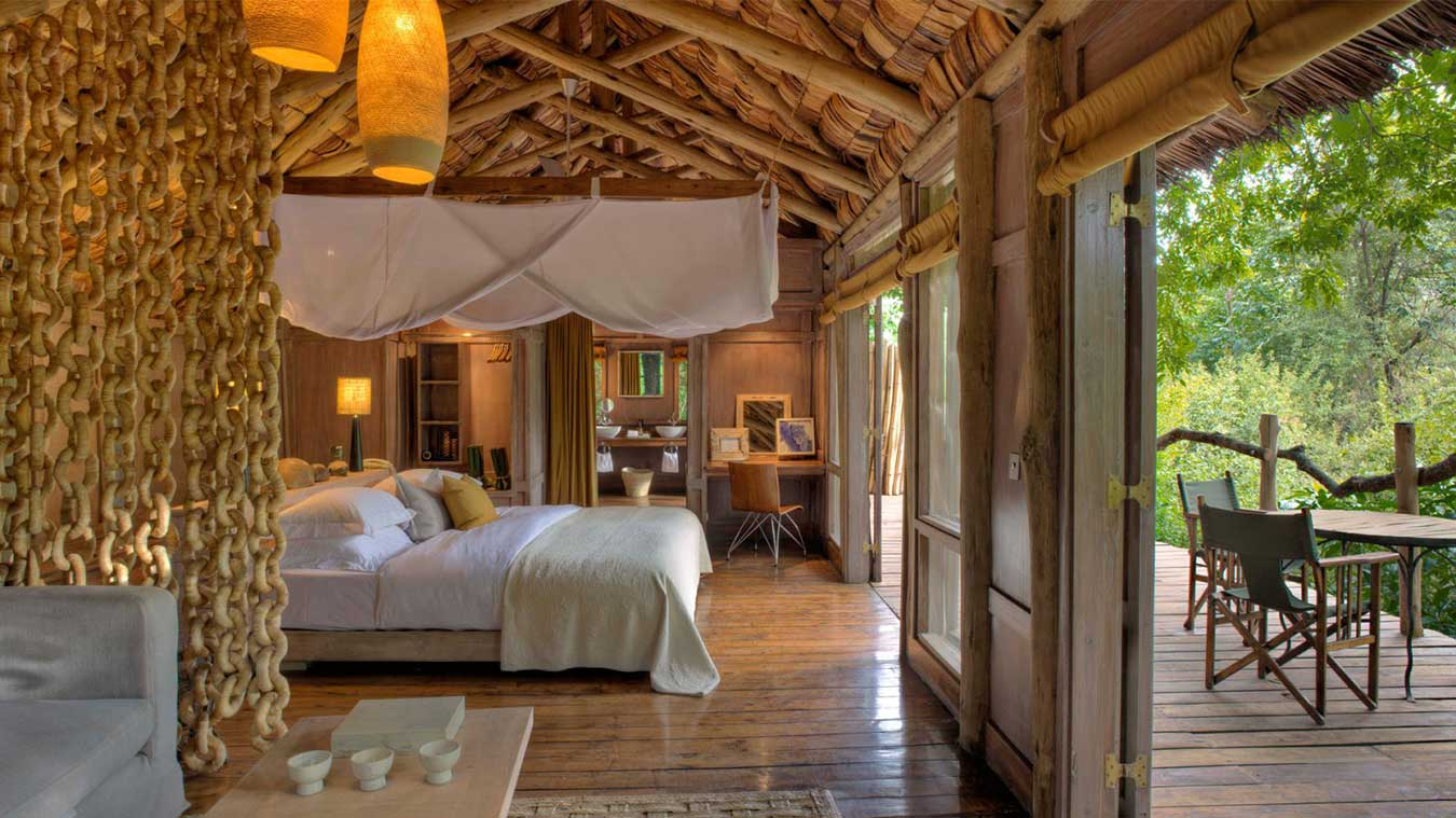 Overlooking a forest boma, or outdoor dining area, lined with traditional dugout canoes, guest areas are characterised by soaring spaces that house local artworks and tactile fabrics.