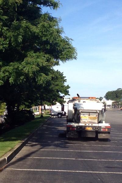 parking lot sweeping truck cleaning asphalt