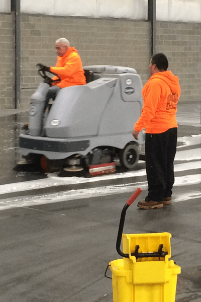 Floor cleaning machine scrubbing concrete surface