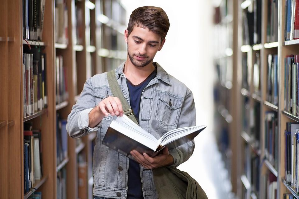 Homem jovem lendo livro em corredor de biblioteca