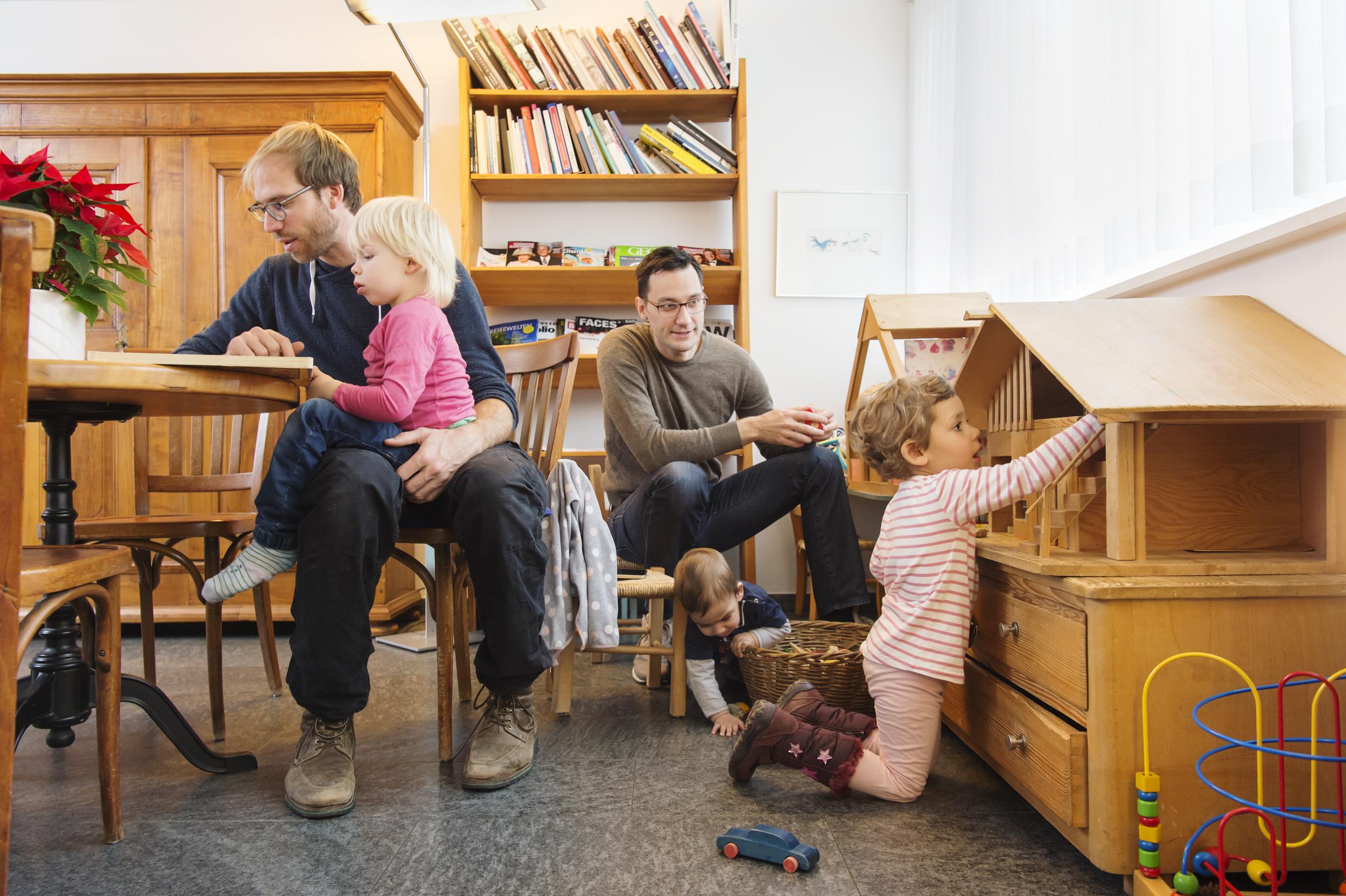 Wartezimmer Situation mit Vätern die mit ihren Kindern warten und spielen.