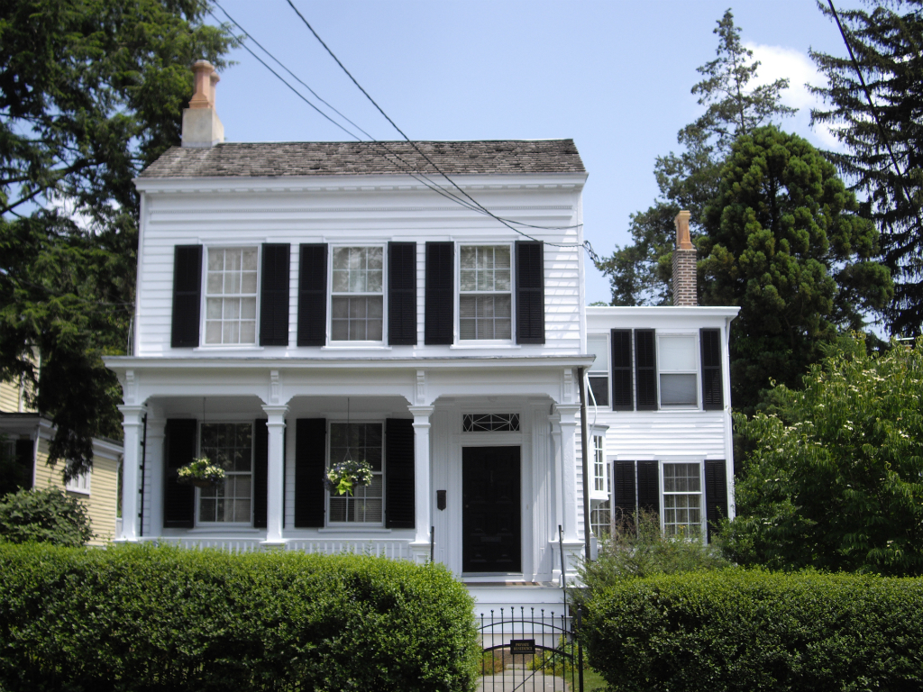 a white colonial home with black shutters on a sunny blue skied day