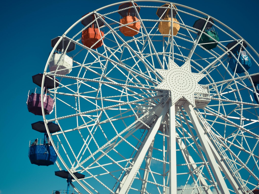 a white ferris wheel against a cloudless blue sky