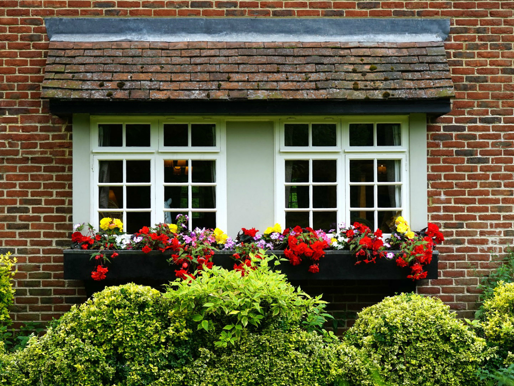 a red brick home with white windows and red flowers in window boxes