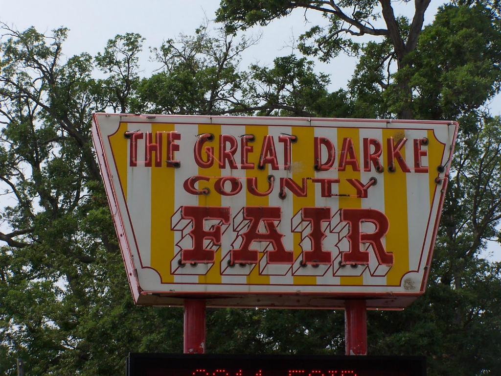 a red and yellow striped sign that reads the great drake county fair in red letters