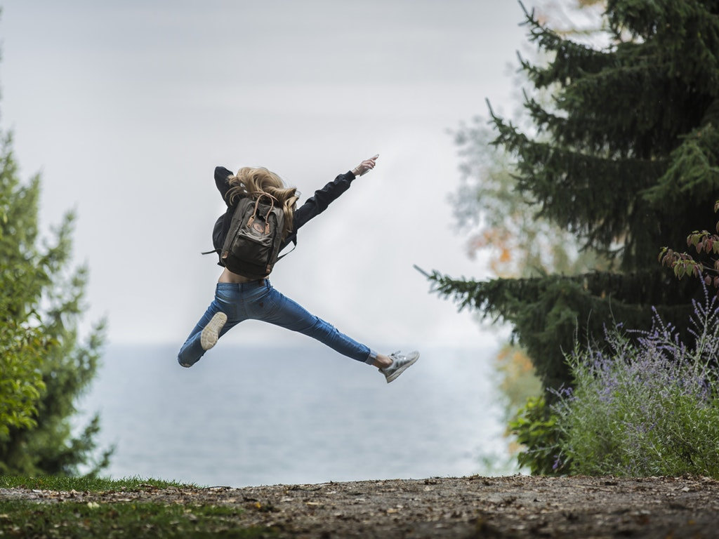 hiker jumping for joy on a trail