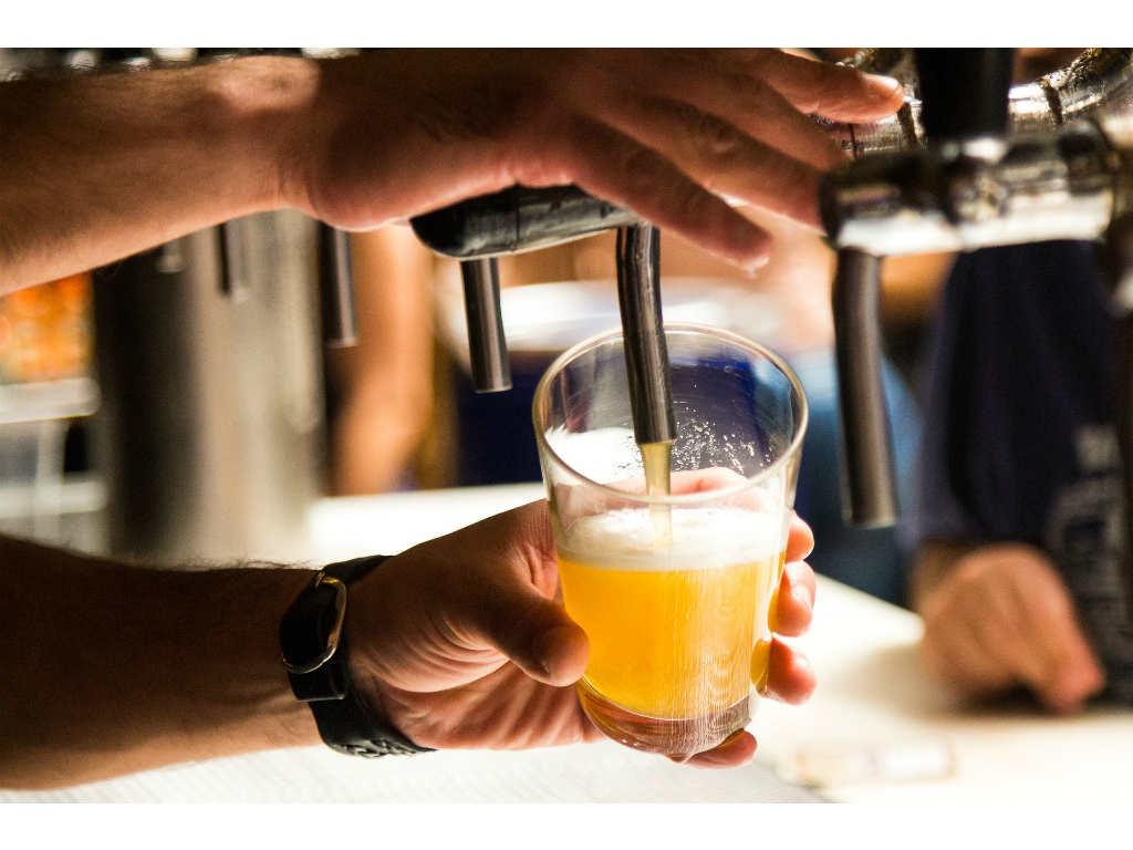 bartender pouring a beer on tap