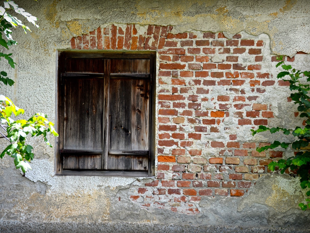 exterior wall with exposed brick and a wooden door