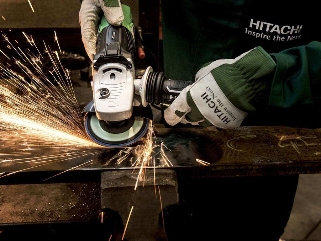 a person cutting with a saw as sparks fly