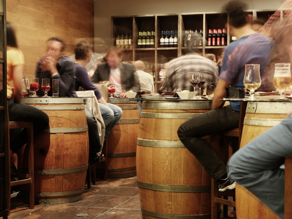 people sitting around barrels at a restaurant in ohio