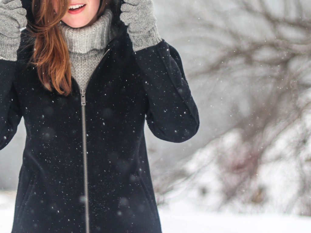 a woman in a winter coat on a snowy day