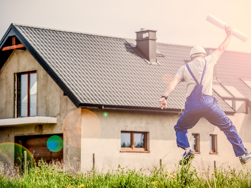 a person jumping for joy by a home