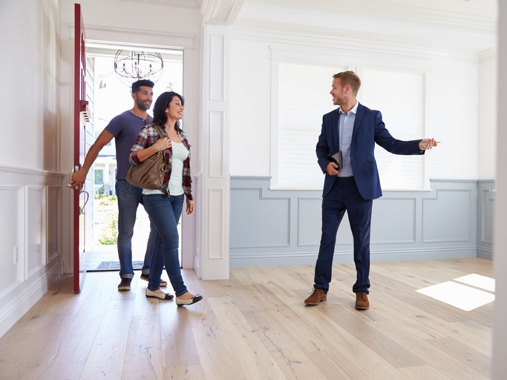 a realtor showing a couple a home